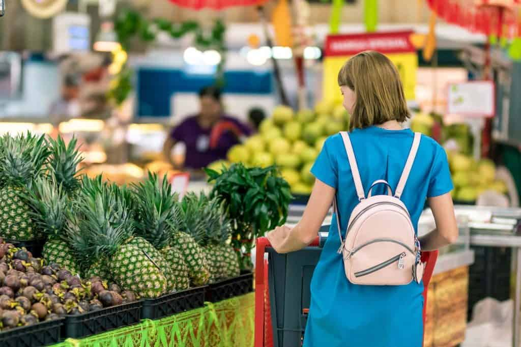 woman standing beside pineapple fruits Grocery Delivery Services: The Best Way To Save Time And Money In 2020