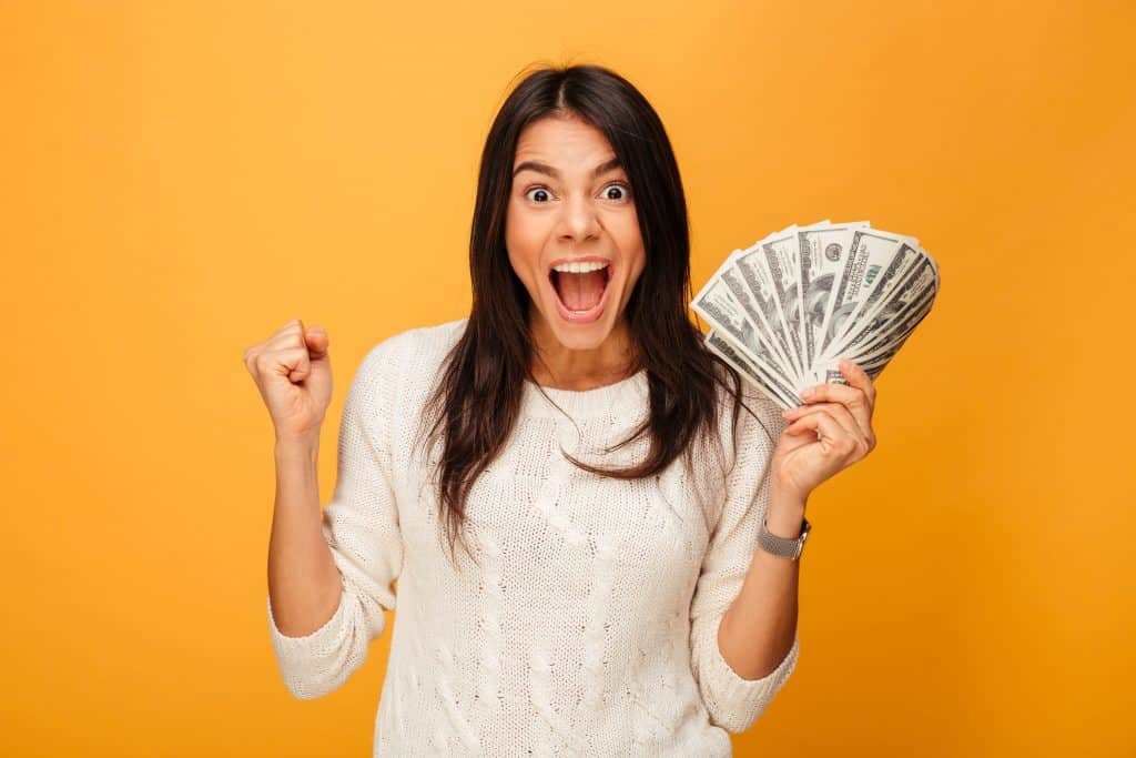 portrait excited young woman holding money banknotes min The Ultimate Guide To Selling On Etsy