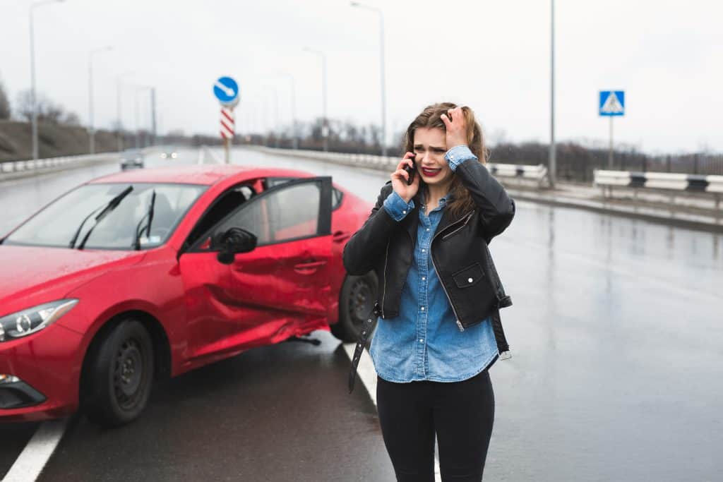 woman calls service standing by red car What To Do After A Minor Car Accident - 5 Simple Steps