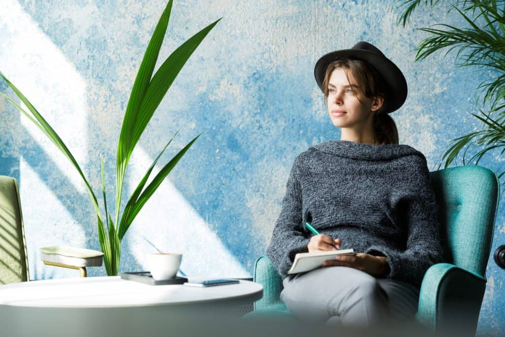 beautiful young woman dressed sweater hat sitting chair cafe table taking notes What You Need to Know About SPACs Before You Invest