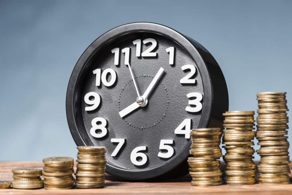 round alarm clock with stack of increasing coins against blue background Mobile Car Detailing [Hire Or DIY?] Ultimate Guide