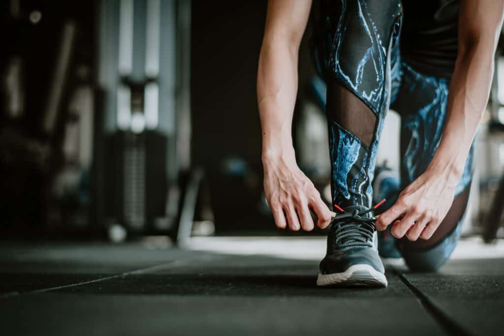 woman tying her shoelaces before exercise The Link Between Health And Financial Wealth